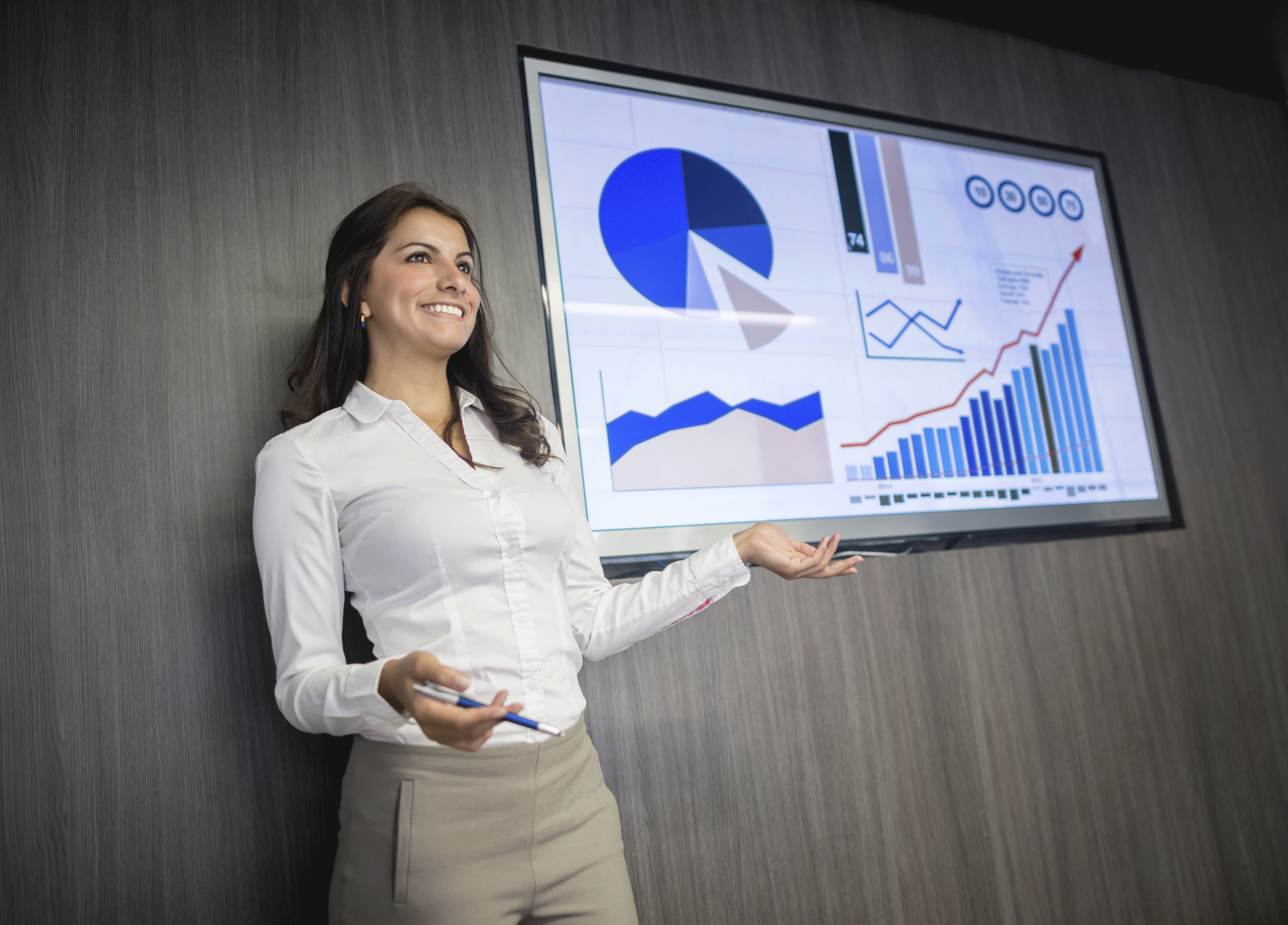 Successful woman making a presentation in a business meeting and showing statistic graphs